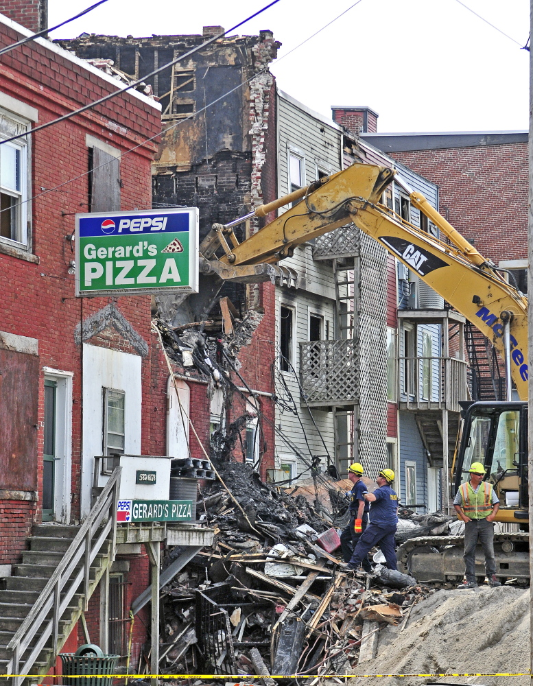 Officials, with the help from an excavator, investigate the scene the morning after a major fire in downtown Gardiner.