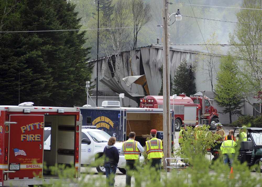 In this May 14, 2010, photo, rescue vehicles stand outside the Black Mag gunpowder plant after an explosion at the plant killed two people in Colebrook, N.H. The owner of the plant, Craig Sanborn, 64, of Maidstone, Vt., was convicted of negligent homicide on Oct. 23, 2013. In June 2015, the New Hampshire Supreme Court heard arguments appealing Sanborn's conviction. David Oldham, a key witness whose testimony helped convict Sanborn, was shot dead in a home invasion in July 2015.