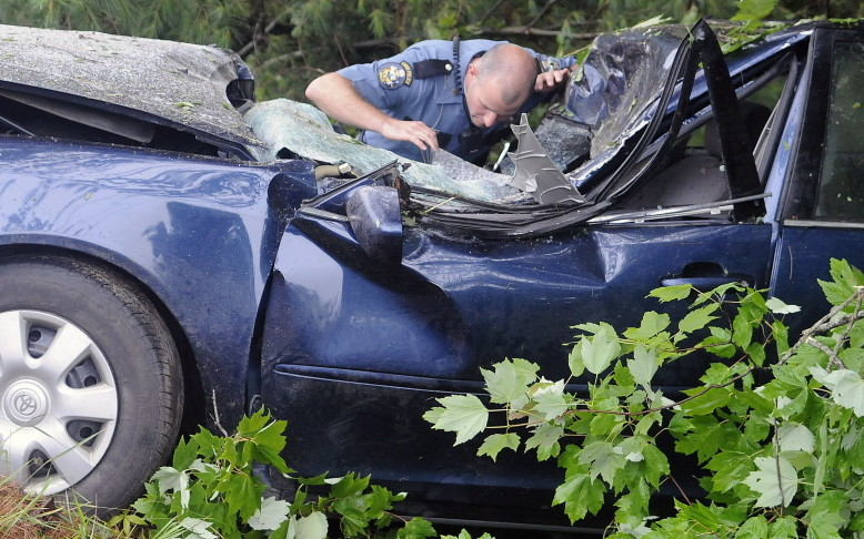 State Trooper Kyle Pelletier searches the interior of a car that struck a tree, killing the operator, on the Plains Road in Litchfield on Sunday.