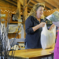 Cynthia Turcotte bags items at the farm stand at Applewald Farm in Litchfield on Sunday. Turcotte and her husband, Tom Fair Jr., welcomed visitors to their 90-acre spread during Open Farm Day.