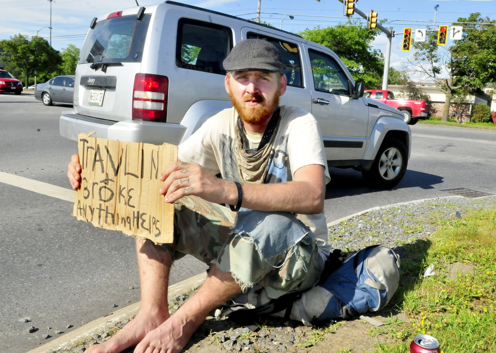 Dewey Wright of Illinois holds a sign asking motorists for help at the end of the Waterville Commons Road in Waterville on Monday.
