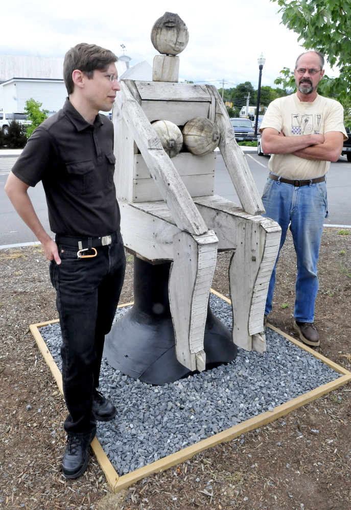 "Dugan Murphy, left, executive director of Main Street Skowhegan, and Steve Dionne of Dionne & Sons Builders speak on Thursday beside a Bernard Langlais sculpture ""Seated Woman."""