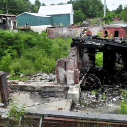 The ruins of the former Cascade Woolen Mill in Oakland on Monday. Two boys were charged with arson for starting a fire in an oil drum at the site. The mill on Cascade Mill Road burned in January 2010.