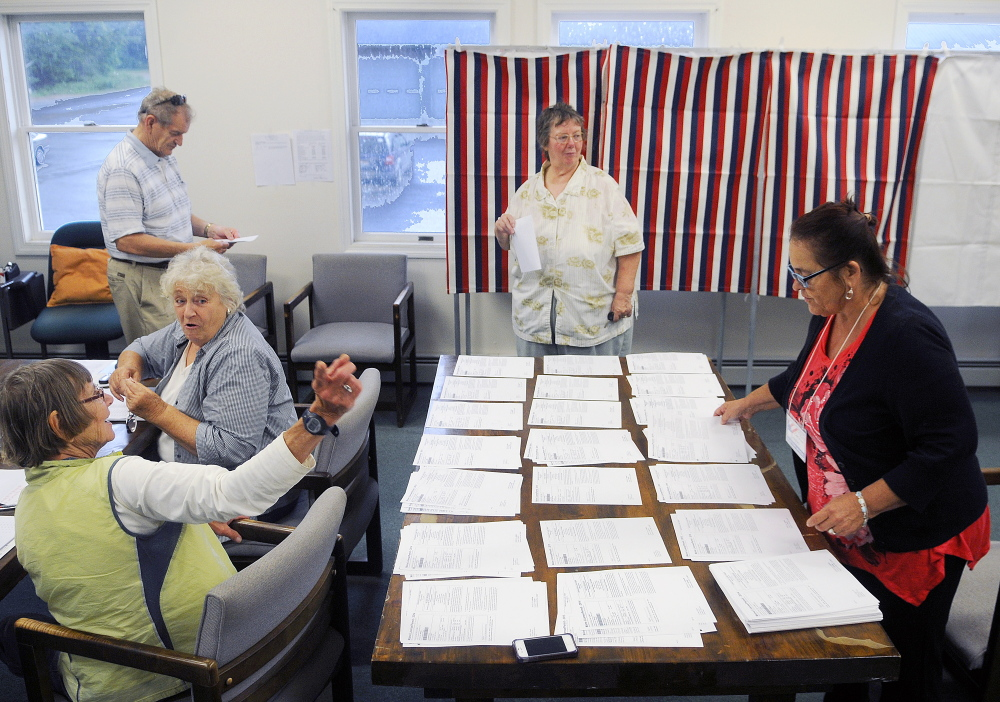 Dian White, left, directs Beverly Chase, second from right, to a ballot box Tuesday in Litchfield as Chase's husband, Daniel, prepares to vote after being issued a ballot by Esther Slattery, second from left. Litchfield, Wales and Sabattus residents were voting on the Regional School Unit 4 school budget.