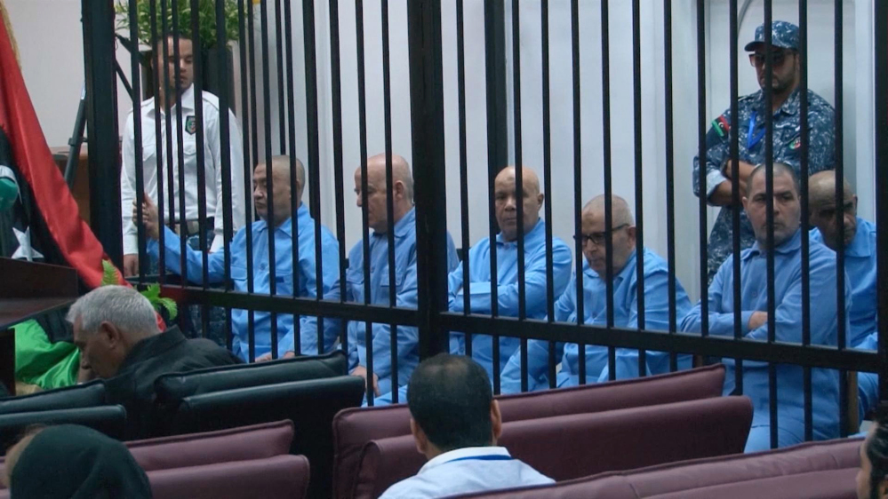 In this image made from AP video, former Libyan officials who served during Moammar Gadhafi's era sit in the defendants' cage during their trial for crimes committed during Libya's 2011 uprising in a courtroom in Tripoli, Libya, Tuesday.