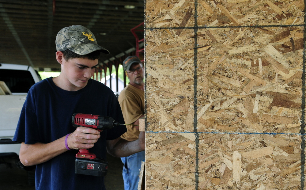 Brandon Kemp helps his father Jeff Kemp build a new ticket booth on Tuesday at the Monmouth Fair grounds.