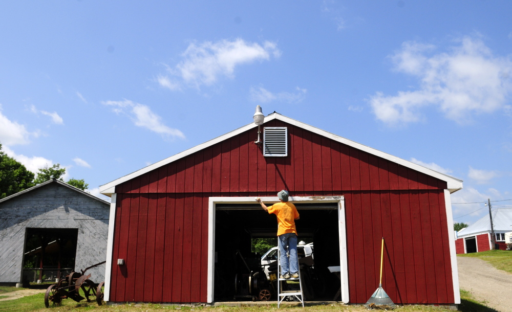 Joy Buzzell paints the door frame of the museum building on Tuesday at the Monmouth Fair grounds.