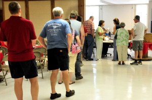 A long line of voters wait for the polls to open at noon Tuesday at the Farmington Community Center to vote on whether to approve the latest Regional School Unit 9 budget.