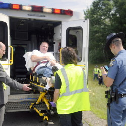 State Police and medics load Trooper Greg Stevens into an ambulance Thursday after his cruiser was struck by a tractor-trailer in the northbound lane of Interstate 295 in Richmond. Stevens walked away from his mangled cruiser. The tractor-trailer crashed and burned in the median. The driver of the tractor-trailer was uninjured, according to police.