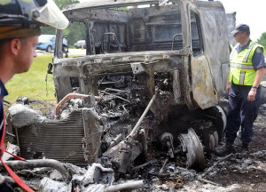 State Police and firefighters examine a tractor- trailer that burned Thursday after an accident on Interstate 295 in Richmond that injured Trooper Greg Stevens.