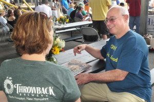 """Chef and keynote speaker Peter Reinhart autographs his book """"Bread Revolution"""" for Erin Allgood at the ninth annual Kneading Conference in Skowhhegan on Thursday."""