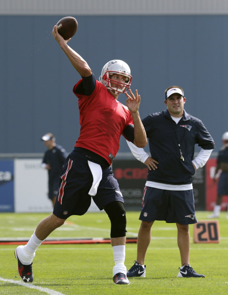 New England Patriots quarterback Tom Brady throws as offensive coordinator Josh McDaniels watches during a training camp practice on Thursday in Foxborough, Mass.