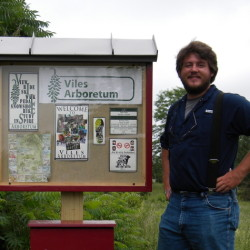 Collections Manager Cooper Van Smith stands with the first kiosk.