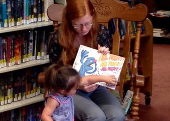 Skowhegan Town Manager Christine Almand, sitting, shares a favorite  story at the Skowhegan Free Public Library while Zoeymarie Rinaldi lends a hand by turning the pages.