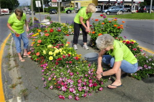 From left, volunteers Terry Borman, Jean Ponitz and Sandy Swartz tend to flowers growing in a traffic island Thursday in downtown Oakland.