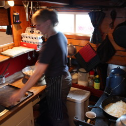 Anne Mahle prepares meals for 30 people at a time in the tiny galley of the Schooner J. & E. Riggin using a wood stove.