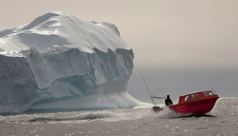 A boat carrying tourists speeds past an iceberg south of Tasiilaq in eastern Greenland.