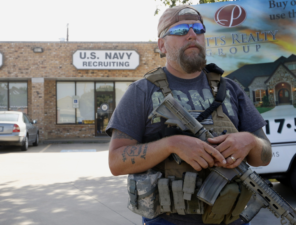 Volunteer Terry Jackson stands guard outside a Navy recruiting station in Cleburne, Texas,