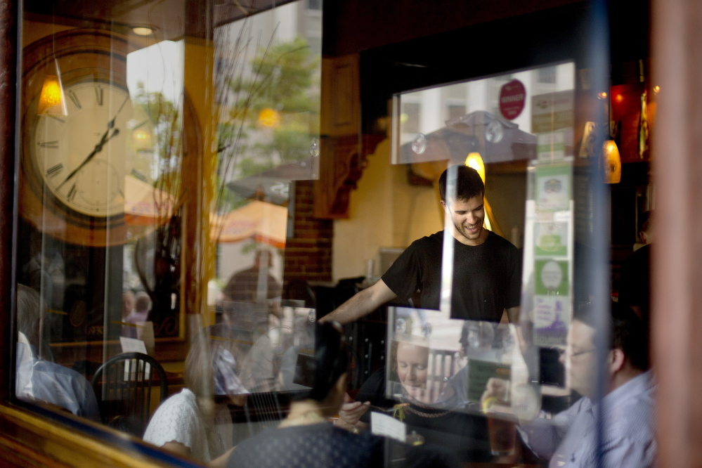 "Portland's Matt Brown, a 26-year-old waiter at David's Restaurant in Monument Square, serves customers during the lunch rush Thursday. Brown's perspective on two proposed minimum wage increases in the city offered a striking contrast to most of the food servers and bartenders in Portland's busy downtown restaurant district: ""Getting paid more? I'm all for it,"" Brown said."