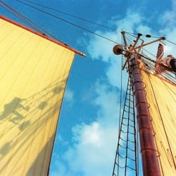 Sunset light casts Greg Hokenson's shadow on the foresail as he climbs the shrouds up the main mast on the Harvey Gamage. Gregory Rec/Staff Photographer