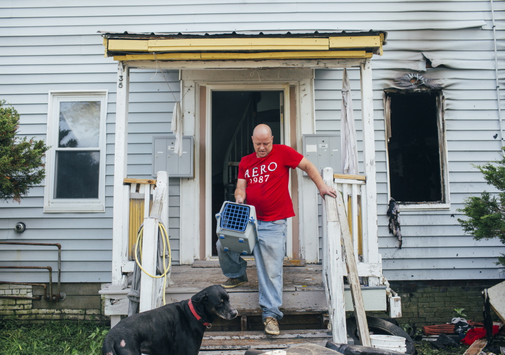 Jason Meyer, with his dog Brooklyn, carries his cat, Kitty, out of his apartment at 135 Bridge St., after a fire overnight displaced residents in Westbrook on Monday. Meyer hadn't seen the cat since the fire started, but Brooklyn found Kitty safe in a closet.