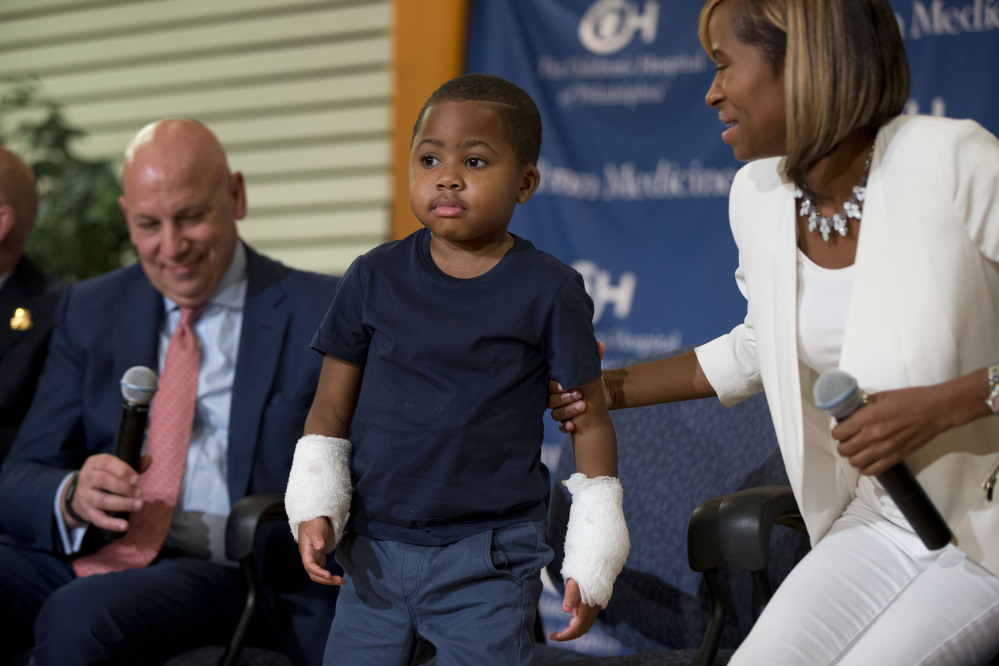 Double-hand transplant recipient Zion Harvey, 8, is accompanied by Dr. L. Scott Levin, left, and his mother, Pattie Ray, at a news conference Tuesday at The Children's Hospital of Philadelphia. Zion is the youngest patient to receive such a transplant.