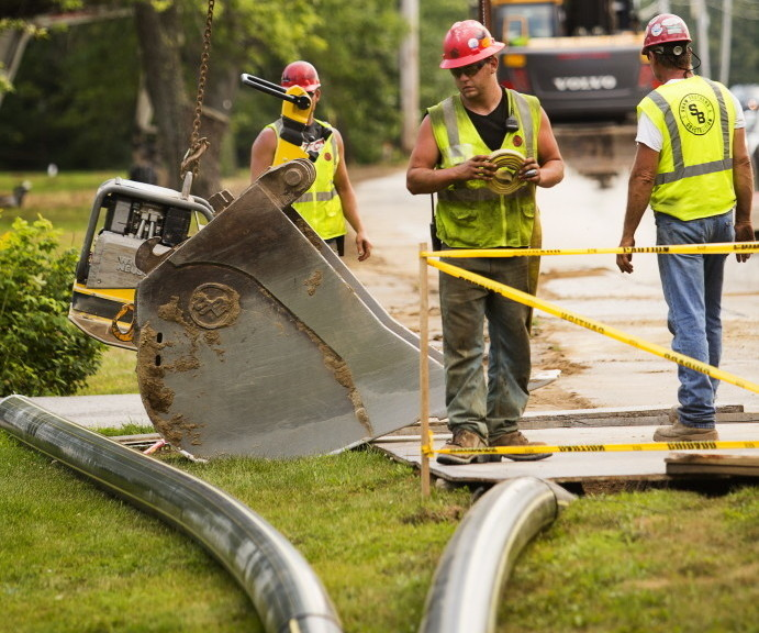 Workers for Summit Natural Gas of Maine install pipeline on Portland Street in Yarmouth. Oil and propane dealers are battling the new competition from gas in Falmouth, Cumberland and Yarmouth with an ad campaign.