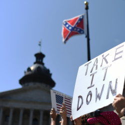 Protesters hold a sign during a rally to take down the Confederate flag at the South Carolina Statehouse, on June 23, 2015, in Columbia, S.C. For years, South Carolina lawmakers refused to revisit the Confederate flag on Statehouse grounds, saying the law that took it off the dome was a bipartisan compromise, and renewing the debate would unnecessarily expose divisive wounds. The Associated Press