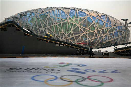 "A worker walks past an ice rink with the logo for Beijing's Winter Olympics bid ahead of Friday's announcement that the Chinese capital  has been selected to host the event. The iconic Beijing National Stadium ""Bird's Nest"" stands in the background. The Associated Press"