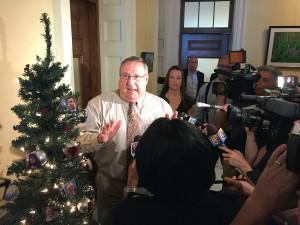 Gov. Paul LePage uses a Christmas tree decorated with pictures of legislative leaders and a rubber pig for props on Wednesday to express his disgust at the $6.7 billion budget that passed both chambers of the Legislature in June. Photo by Kevin Miller / Staff Writer