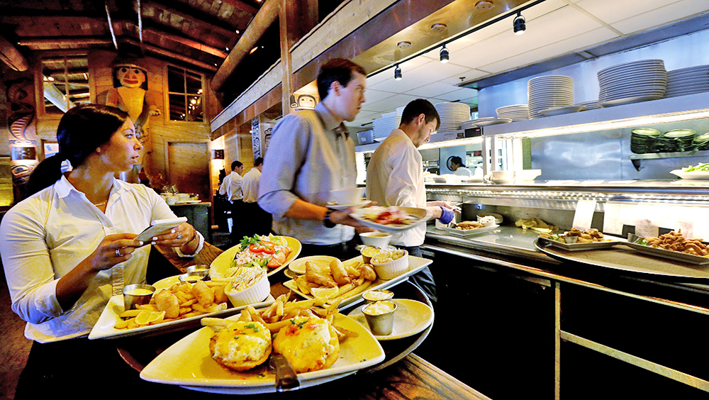 Workers prepare to bring food orders to customers at an Ivar's restaurant in Seattle. The restaurant's revenue is up 20 percent, says the company's president, Bog Donegan, who served on the mayoral committee that drafted the minimum wage law. The Associated Press