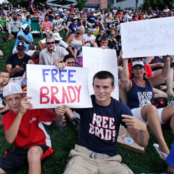 New England Patriots fans hold signs supporting quarterback Tom Brady during training camp in Foxborough, Mass., Thursday. The Associated Press