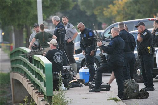 Police gather to contain a reported lion in Milwaukee on Monday. Officers armed with rifles and Department of Natural Resources staff carrying tranquilizer guns searched a ravine and surrounding neighborhood for an elusive lion-like animal after police were among those who spotted the big cat. Michael Sears/Milwaukee Journal Sentinel via AP