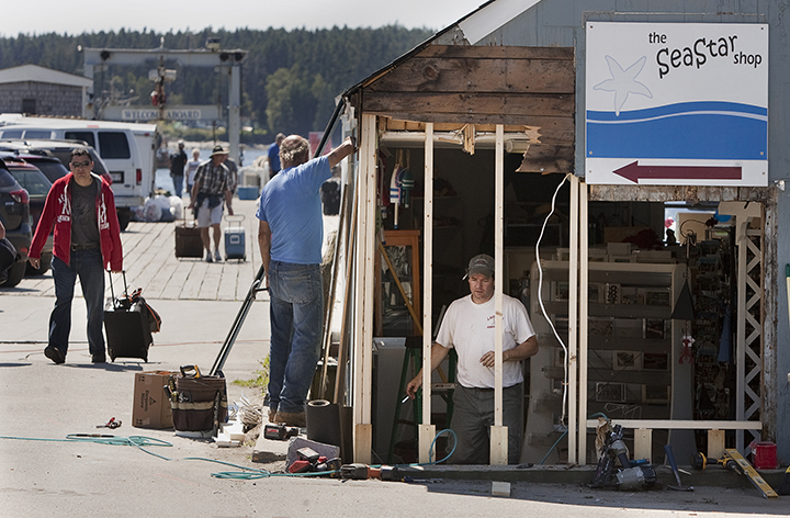 Tim Harris and  Joseph Richardi of Port Clyde repair the damage to a shop at the scene of a fatal auto pedestrian accident at the wharf in Port Clyde in this 2013 file photo. Carl D. Walsh/Staff Photographer