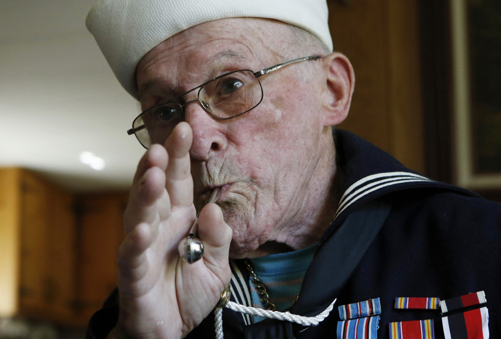 WWII veteran Conrad Lebourdais demonstrates whistle signals he used during his time on board a ship in the Pacific Theater in World War II. Joel Page/Staff Photographer