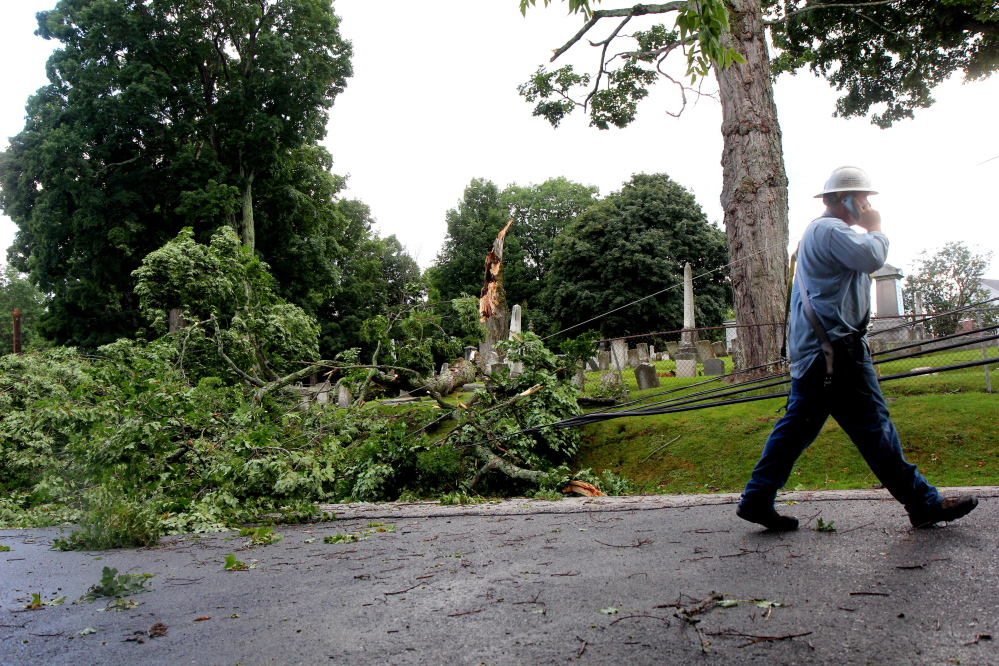 Central Maine Power Co. crewman Sam Pottle walks past debris that knocked out a row of power lines Saturday afternoon on Morton Street in Winthrop during a thunderstorm that hit Winthrop and nearby communities.