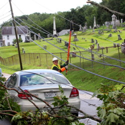 Central Maine Power Co. crewman Wayne Piper installs a ground wire Saturday on Morton Street in Winthrop so a tree crew can safely remove limbs that took out power lines during a thunderstorm that afternoon, and caused the temporary closure of the street.