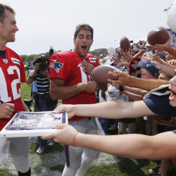 New England Patriots quarterbacks Tom Brady (12) and Jimmy Garoppolo, center, sign autographs during training camp Saturday in Foxborough, Mass.