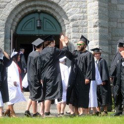 Gavin Hayford, left center, high-fives fellow graduate Eric Clark, right center, on Saturday outside Moody Chapel at the Good Will-Hinckley campus in Hinckley, just before the Maine Academy of Natural Sciences commencement ceremony.