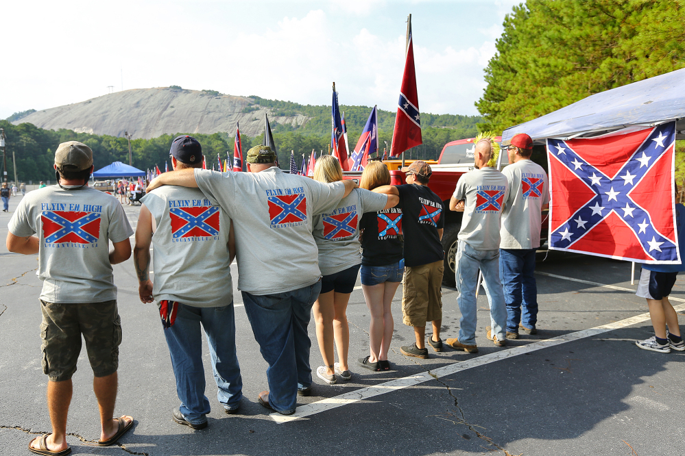 """The """"Flyin' Em High"""" group from Loganville wear shirts and hang flags while participating in a pro-Confederate flag rally at Stone Mountain Park in Stone Mountain, Ga., on Saturday."""