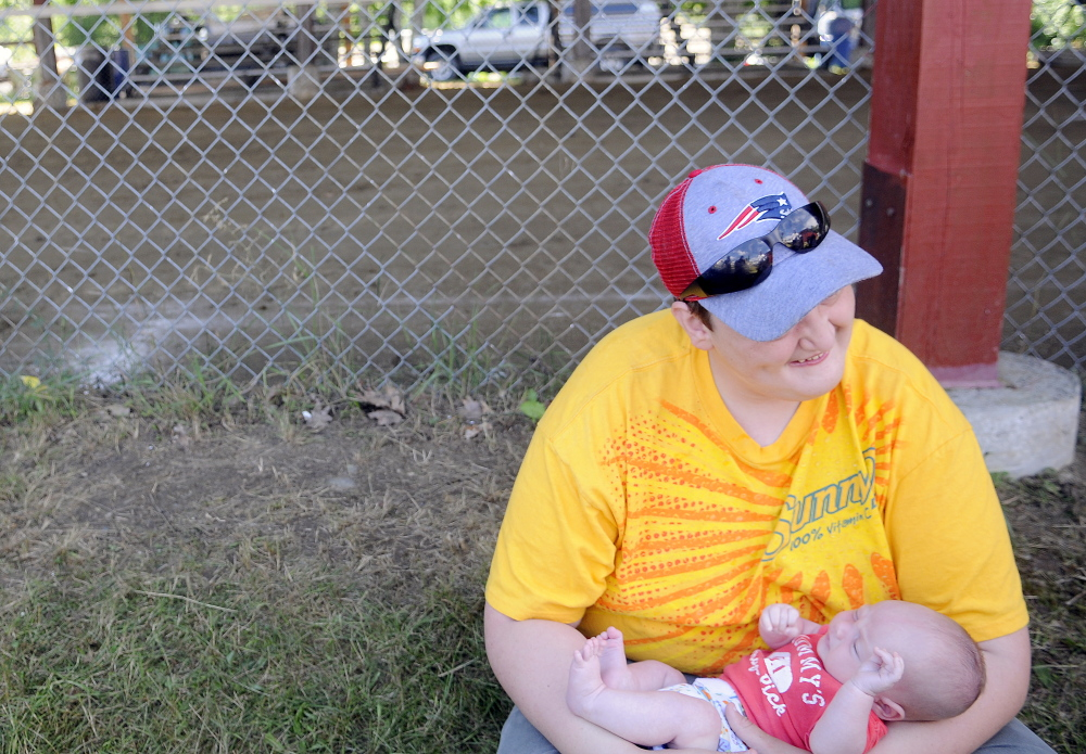 Kristoff Fox, 17, of Monmouth, holds his month-and-a-half old nephew, Jeremiah Fox, of Monmouth, on Sunday outside the pulling ring at the Monmouth Fair. Four generations of Foxes volunteered and attended the agricultural exhibition.