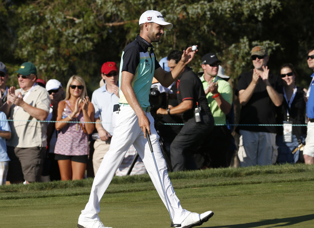 Troy Merritt tips the ball to the crowd after a birdie on the 16th hole during the final round of the Quicken Loans National on Sunday at the Robert Trent Jones Golf Club in Gainesville, Va. Merritt won the tournament at 18-under-par.