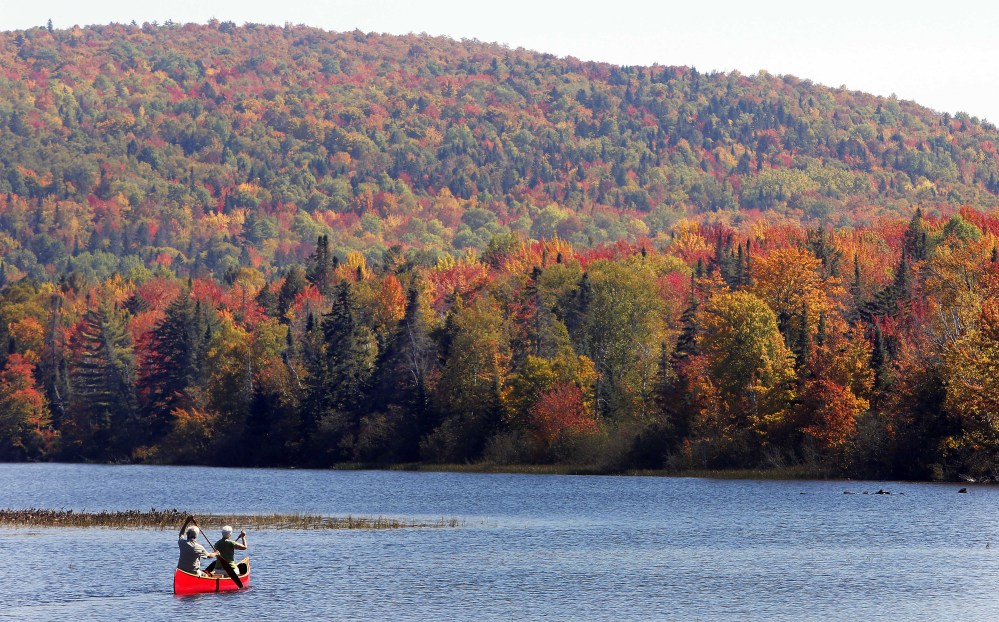 In this Sept. 27, 2014 file photo, Brad and Sue Wyman paddle their 1930's Old Town Guide canoe along the Androscoggin River as leaves display their fall colors north of the White Mountains in Dummer, N.H. Critics of proposals to import relatively clean hydropower from Quebec into the Northeastern United States worry that transmission lines will despoil New Hampshire's natural beauty with power lines.