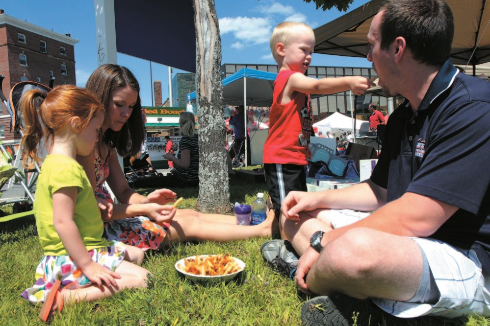 Liam Rose, 3, gives his dad, Phil, a french fry while enjoying the Taste of Waterville last year with his four-year-old sister Isabelle and mother, Heather.