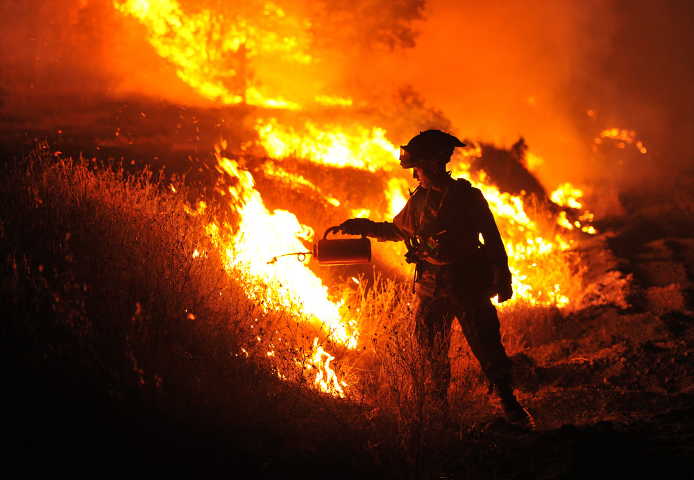 CalFire firefighter Bo Santiago lights a backfire as the Rocky fire burns near Clearlake, Calif., on Monday.
