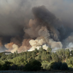 A plume of smoke rises above a hillside as the Rocky Fire burns near Clearlake, Calif., on Monday
