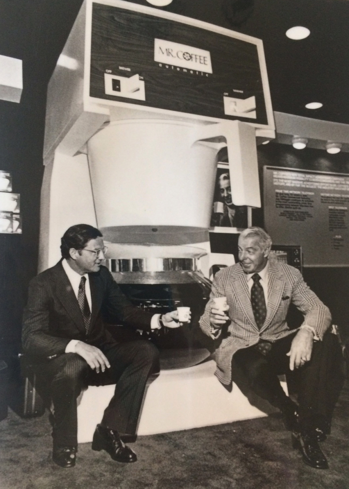 This 1977 photo provided by the Marotta family shows Vincent Marotta, left, and Joe DiMaggio sitting on a large Mr. Coffee machine in Chicago.