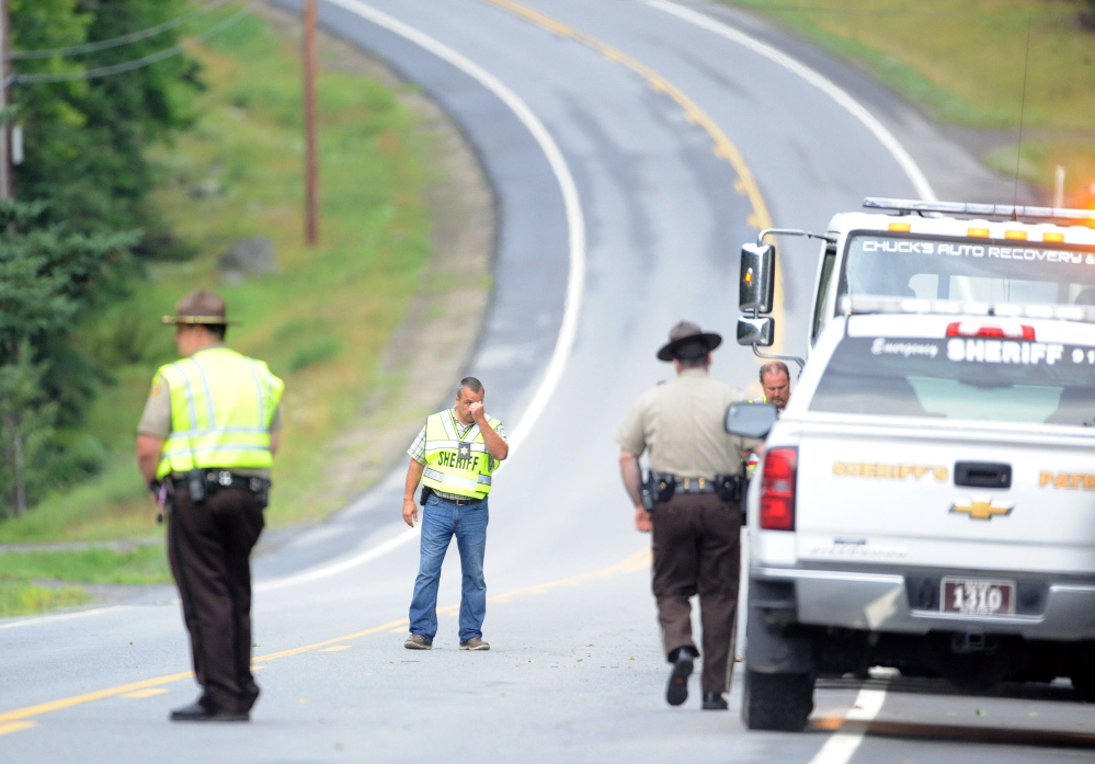 Police gather on U.S. Route 201 in West Forks Plantation, where Martin Poulin and Francine Dumas, both of Quebec, were found dead in their car on Tuesday. The couple had been missing since they left Quebec for a wedding a week ago. They were found by family members, who had been looking for them the past week.