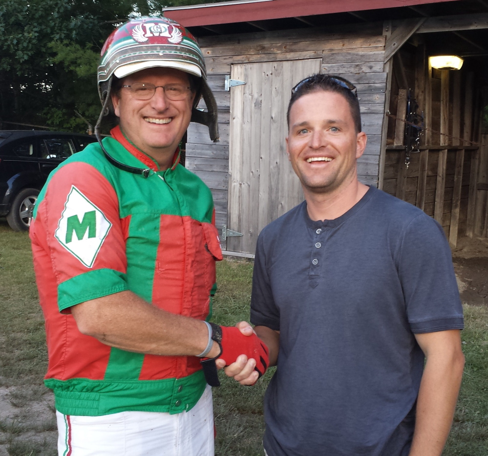 Contributed photo/MHHA   Yannick Gingras, right, congratulates Gary Mosher in the paddock of the Topsham Fairgrounds on Tuesday after Mosher won his 6,000th career race.