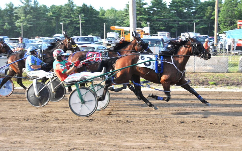 Contributed photo/Shelley Gilpatrick   Gary Mosher, riding So What Who Cares, crosses the finish line at the Topsham Fairgrounds on Tuesday to win his 6,000th career race.